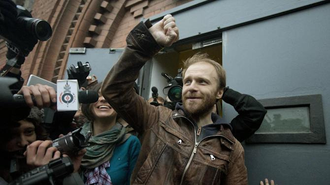 """Russian freelance photographer Denis Sinyakov, center, rises his fist outside the gates of """"Kresty"""" St. Petersburg prison, after he was released in St. Petersburg, Russia, Thursday, Nov. 21, 2013. Two more of the 30 people arrested by Russia following a Greenpeace protest in the Arctic two months ago have been freed on bail. Sinyakov and activist Andrei Allakhverdov walked out of a detention center on Thursday. The 30 were arrested in September after a Greenpeace ship, the Arctic Sunrise, entered Arctic waters despite Russian warnings. (AP Photo/Pavel Golovkin)"""
