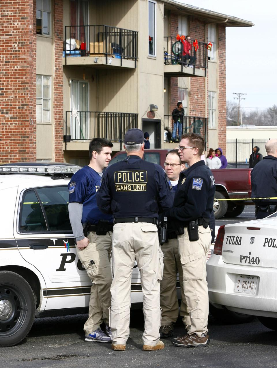 Officers from the Tulsa Police Department's Gang Unit gather after a quadruple homicide at Tulsa's Fairmont Terrace apartment complex on Monday, Jan. 7, 2013.  Four women were found shot to death inside an apartment, where a 4-year-old boy was also found unharmed.  (AP Photo/Tulsa World, Matt Barnard )   TV OUT; TULSA OUT