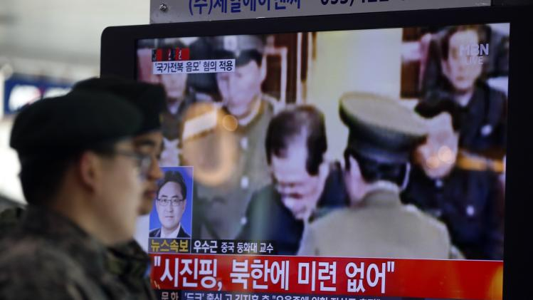 South Korean soldiers walk past a television showing reports on the execution of Jang Song Thaek, in Seoul
