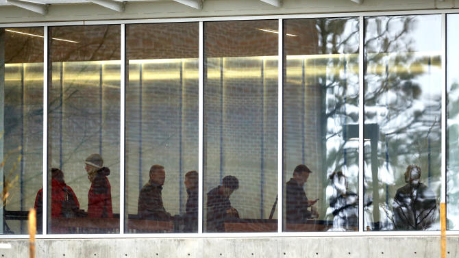 People wait in a security line inside the entrance to the Arapahoe County Justice Center, on the first day of the trial of James Holmes, in Centennial, Colo., Monday, April 27, 2015. Holmes acknowledges killing 12 people and wounding 70 more inside a packed movie theater on July 20, 2012, but has pleaded not guilty by reason of insanity. (AP Photo/Brennan Linsley)
