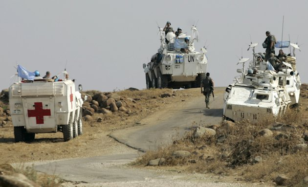 Spanish United Nations peacekeepers atop armored vehicles patrol the border in the southeastern Wazzani River area, Lebanon, Monday, Aug. 1, 2011. Israeli and Lebanese troops briefly exchanged fire Monday on the countries' border, a volatile area where tensions can easily reignite hostilities between the two nations. (AP Photo/Lutfallah Daher)