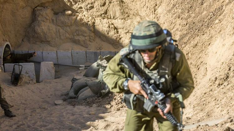 An Israeli army officer walks up at the entrance of a tunnel said to be used by Palestinian militants for cross-border attacks