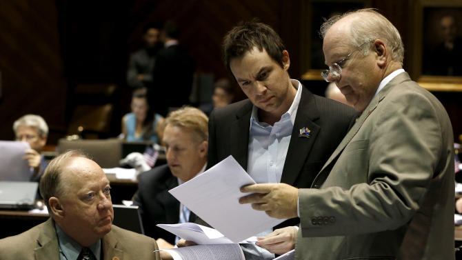 House Speaker Rep. Andy Tobin, R-Paulden, right, confers with Speak Pro-Tempore Rep. J.D. Mesnard, R-Chandler, and Majority Whip Rep. Rick Gray, R-Sun City, left, in a special session budget battle for Medicaid funding on Wednesday, June 12, 2013, in Phoenix. The Arizona Legislature is on track to pull an all-nighter and work into Thursday to finish a state budget and approve Medicaid expansion. (AP Photo/Ross D. Franklin)
