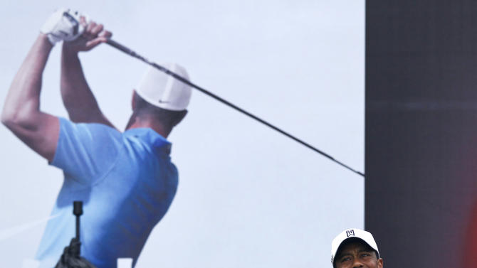 Tiger Woods lets go of his club after his tee shot on the first hole during his 18-hole medal-match against Rory McIlroy at the Lake Jinsha Golf Club in Zhengzhou, in central China's Henan province, Monday, Oct. 29, 2012. (AP Photo/Alexander F. Yuan)