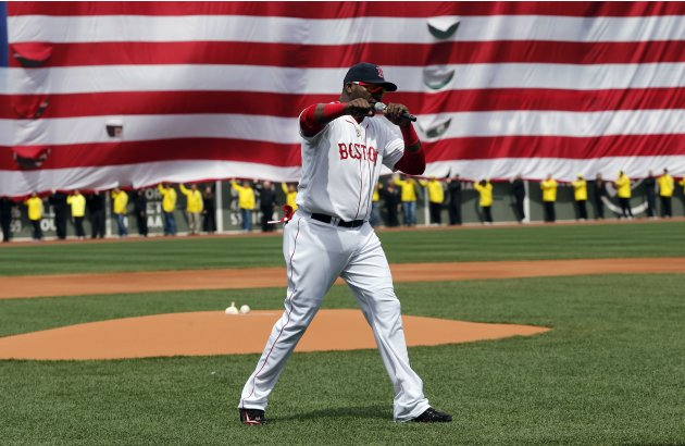 Boston Red Sox's David Ortiz pumps his fist in front of an Amarican flag and a line of Boston Marathon volunteers, background, after addressing the crowd before a baseball game between the Boston