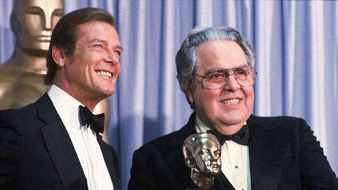 "FILE - In this March 29, 1982 file photo, Albert ""Cubby"" Broccoli, producer of the ""James Bond"" series, holds the Thalberg Award he received for his work at the Academy Awards, in Los Angeles.  Roger Moore, left, British actor who plays secret agent 007 James Bond, made the presentation.  (AP Photo/Reed Saxon, File)"