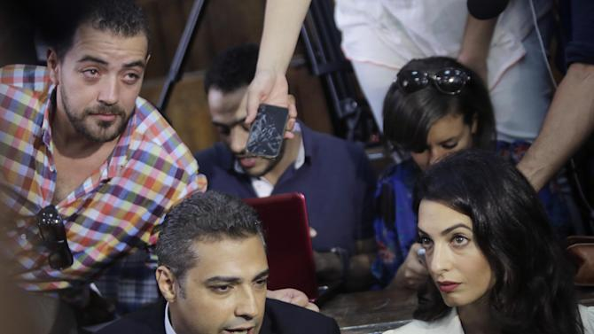 Canadian Al-Jazeera English journalist Mohammed Fahmy, left, his lawyer Amal Clooney and his Egyptian colleague Baher Mohammed, at top left, speak to media before their verdict in a courtroom in Tora prison in Cairo, Egypt, Saturday, Aug. 29, 2015. An Egyptian court on Saturday sentenced three Al-Jazeera English journalists to three years in prison, the last twist in a long-running trial criticized worldwide by press freedom advocates and human rights activists. (AP Photo/Amr Nabil)