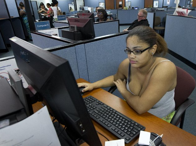 In this Friday, Sept. 7, 2012, photo, Melina Abrey sits at a computer station, doing job applications, at WorkForce One in Hollywood, Fla. The number of Americans seeking unemployment benefits jumped to 382,000 last week, the highest level in two months. (AP Photo/J Pat Carter)
