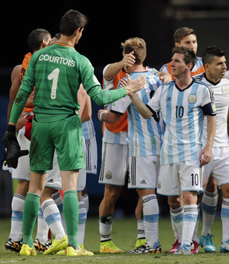 Argentina's Lionel Messi, right, greets Belgium's goalkeeper Thibaut Courtois at the end of the World Cup quarterfinal soccer match between Argentina ...