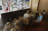Foreign tourists spend time at a cafe, fortified with sandbags to stop floodwaters, in Bangkok, Thailand, Friday, Nov. 11, 2011. Thailand is once again in tourist turmoil as floods linger, but ever resilient industry unfazed. (AP Photo/Altaf Qadri)