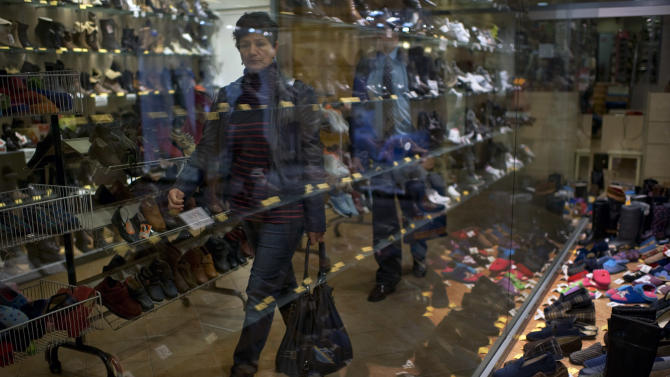 """A woman passes in front of a shoe shop promoting their products, in Pamplona, northern Spain, Monday Nov. 14 , 2011. The European Union warned last Thursday that the 17-country eurozone could slip into """"a deep and prolonged recession"""" next year as the debt crisis shows alarming signs of spinning out of control. Spain has suffered a long economic crisis with more than five millions unemployed. (AP Photo/Alvaro Barrientos)"""