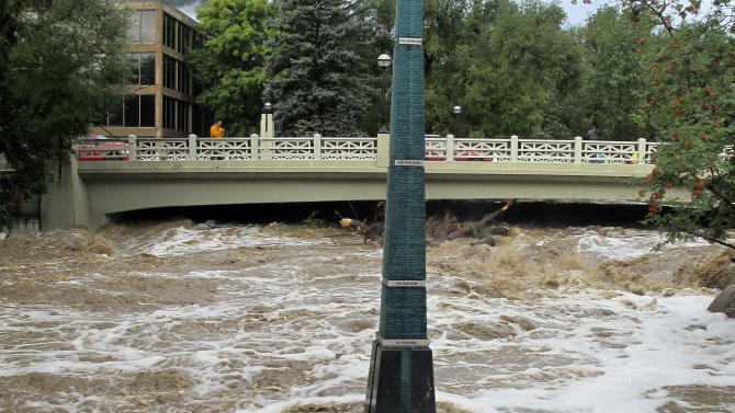Rain-swollen Boulder Creek flows around a marker that shows historic flood levels on Friday morning, Sept. 13, 2013, in Boulder, Colo. City officials ordered an evacuation of thousands of residents along the creek the night before. Coffee-colored floodwaters cascaded downstream from the Colorado Rockies on Friday, spilling normally scenic mountain rivers and creeks over their banks and forcing thousands more evacuations(AP Photo/Ben Neary)