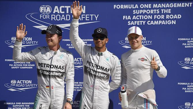 Valtteri Bottas (right) on the podium with first placed Lewis Hamilton (centre) and runner-up Nico Rosberg after taking third place in qualifying on September 6, 2014 for the Italian Grand Prix