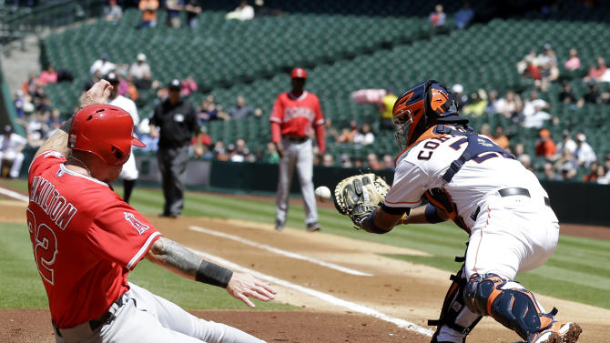 Los Angeles Angels' Josh Hamilton (32) slides into home to score as Houston Astros catcher Carlos Corporan (22) reaches for the ball in the first inning of a baseball game Monday, April 7, 2014, in Houston. Hamilton and Albert Pujols scored on a Howie Kendrick single. (AP Photo/Pat Sullivan)