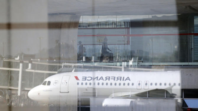 An Air France plane is reflected on a window  at Paris Charles de Gaulle airport, in Roissy, near Paris, Monday, Sept. 15, 2014. Pilots for Air France have kicked off a weeklong strike, angry that the airline is shifting jobs and operations to a low-cost carrier to better keep up with competition. (AP Photo/Christophe Ena)