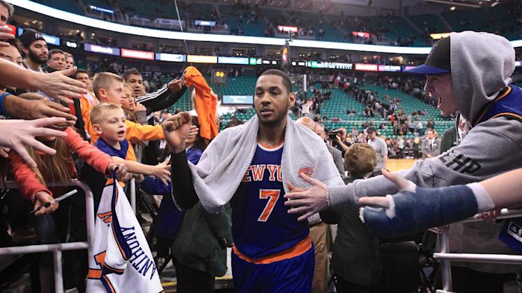 Fans reach for New York Knicks' Carmelo Anthony (7) as he walks off the court following their NBA basketball game against the Utah Jazz Monday, March 31, 2014, in Salt Lake City. The Knicks won 92-83