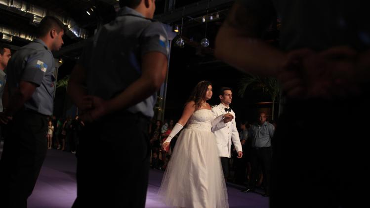 A 15-year-old girl is escorted by a police officer as she arrives to her debutante ball in Rio de Janeiro