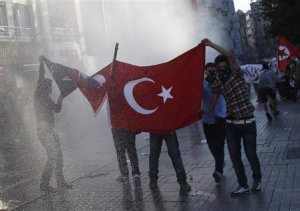Protesters hold a Turkish flag as riot police use a water cannon to disperse them at Taksim square in central Istanbul