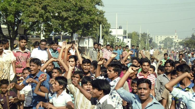 Garment workers shout slogans as they block a street during a protest demanding higher wages in Gazipur