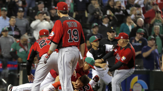 Canada's Joey Votto watches a fight between teammates and Mexico during the ninth inning of a World Baseball Classic game, Saturday, March 9, 2013, in Phoenix. (AP Photo/Matt York)