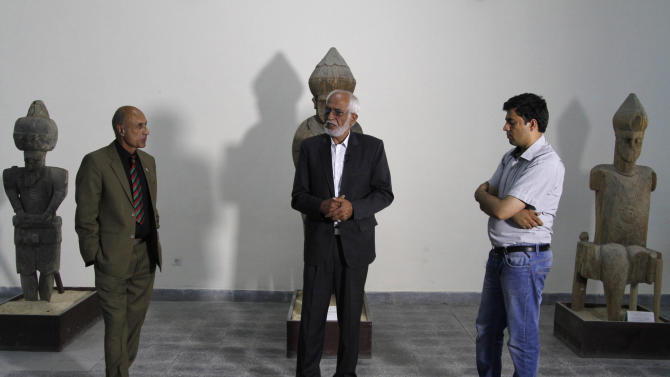 National Museum of Afghanistan director Omara Khan Massoudi, center, speaks to reporters in Kabul, Afghanistan, Friday, June, 28, 2013. Looters stole tens of thousands of artifacts from the National Museum of Afghanistan during the country's civil war in the 1990s, and then thousands more were destroyed by the Taliban when they took power. Now the museum is slowly coming back to life, helped by millions of dollars in U.S. and other foreign aid. Every day 300 to 400 visitors a day come to see the collections of sculptures, jewelry, coins and other artifacts dating from the Stone Age through the 20th century.(AP Photo/Ahmad Jamshid)