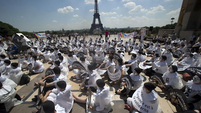 """Demonstrators dressed as mime artists hold placards which read """"no to the euthanasia of elderly people, solidarity is urgent"""", at Trocadero plaza in Paris, Tuesday June 24, 2014. One of France's top courts will rule Tuesday on whether to cut the life support of a 38-year-old in a vegetative state, in a case that has torn his family apart. The State Council is due to make the sensitive call on the case of Vincent Lambert, who has been a quadriplgic since a car crash in 2008. Eiffel Tower is in the background. (AP Photo/Michel Euler)"""