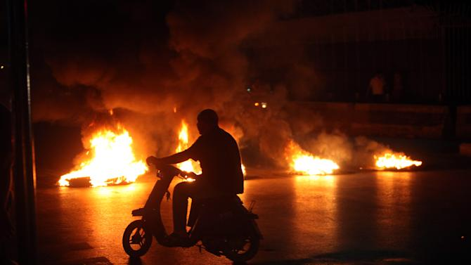 A man on a motorbike passes burning tires laid by Sunni protesters, angry at the killing of Brig. Gen. Wissam al-Hassan, to block a road in Beirut, Lebanon, Friday, Oct. 19, 2012.  A car bomb ripped through Beirut on Friday, killing a top security official and several others, shearing the balconies off apartment buildings and sending bloodied residents staggering into the streets in the most serious blast the Lebanese capital has seen in four years. Dozens of people were wounded in the attack, which the state-run news agency said targeted the convoy of Brig. Gen. Wissam al-Hassan, a top security official in Lebanon. (AP Photo/Bilal Hussein)