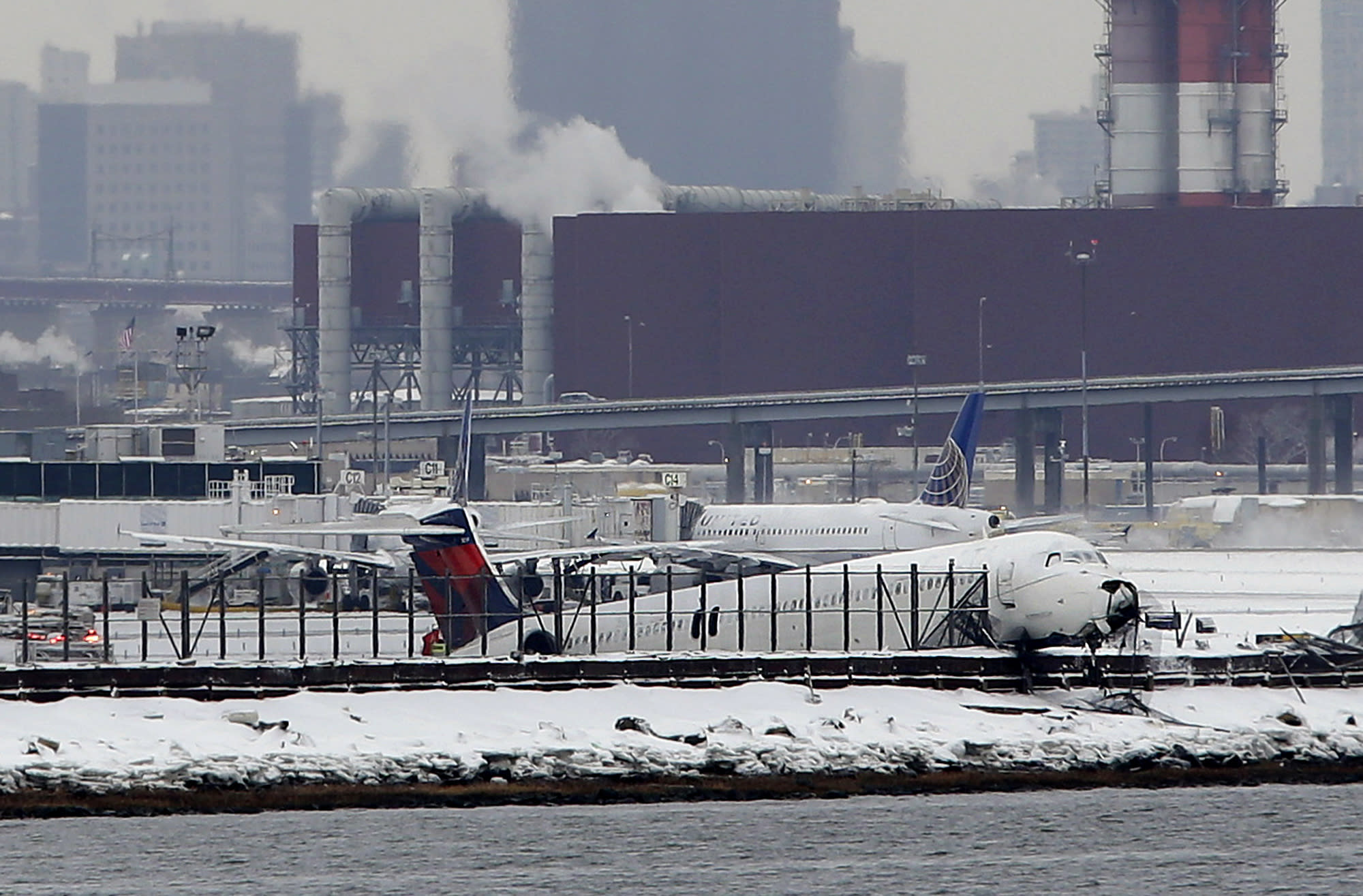 Plane skids off LaGuardia runway, slams into fence near bay