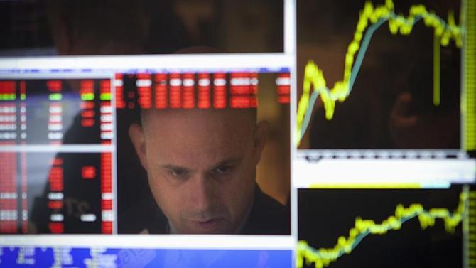 A trader is reflected in his computer screen on the floor of the New York Stock Exchange at the market open in New York