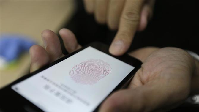 File photo of a journalist testing the the new iPhone 5S Touch ID fingerprint recognition feature in Beijing