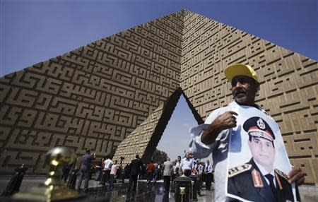 A man holds a poster Army Chief Sisi at the tomb of late Egyptian President Sadat, in Cairo