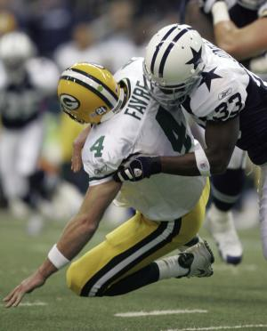 FILE - Green Bay Packers quarterback Brett Favre (4) is tackled by Dallas Cowboys cornerback Nathan Jones (33) in the second quarter of their NFL football game, in this Nov. 29, 2007 file photo taken in Irving, Texas. Favre injured his arm as he fell to the turf and left the game. He was replaced by Aaron Rodgers because of the injuries to his elbow and shoulder. (AP Photo/LM Otero)