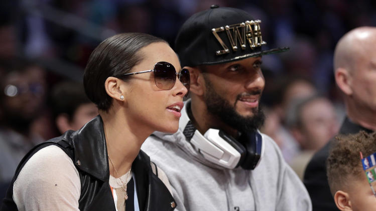 Singer Alicia Keys, left, and her husband Swizz Beatz sit courtside during NBA All-Star Saturday Night basketball in Houston on Saturday, Feb. 16, 2013. (AP Photo/Eric Gay)