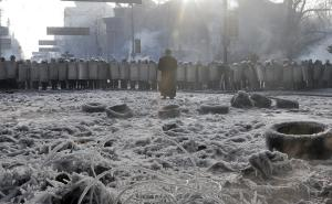 An Orthodox Christian priest prays in front of riot…