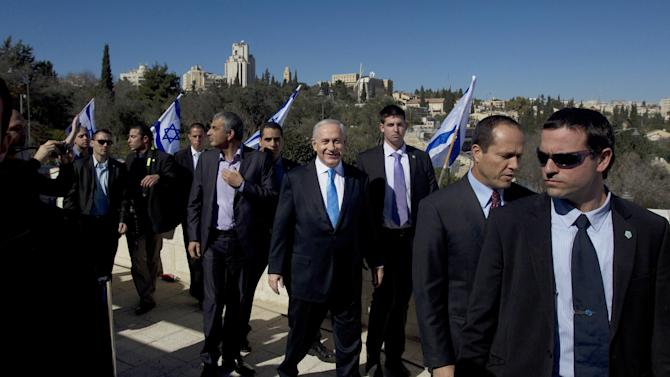 Israeli Prime Minister Benjamin Netanyahu, center, is surrounded by bodyguards as he arrives with Jerusalem Mayor Nir Barkat, second right, and Likud party member Moshe Kahlon, left, to brief the media in Jerusalem, Monday, Jan. 21, 2013. General elections in Israel will be held Tuesday, Jan. 22, 2013. (AP Photo/Sebastian Scheiner)