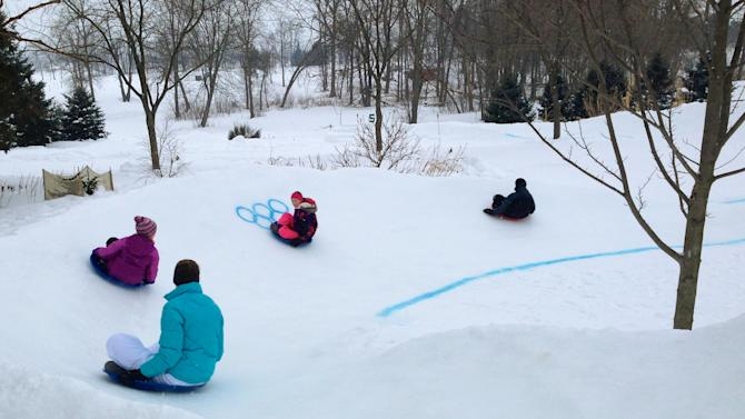 In a Friday Feb. 14, 2014 photo people enjoy the sled track that the the Baker and Hines family built on a backyard hill in Mason, Mich. The course has a rendering of the Olympic rings. (AP Photo/WILX-TV, Amanda Malkowski)