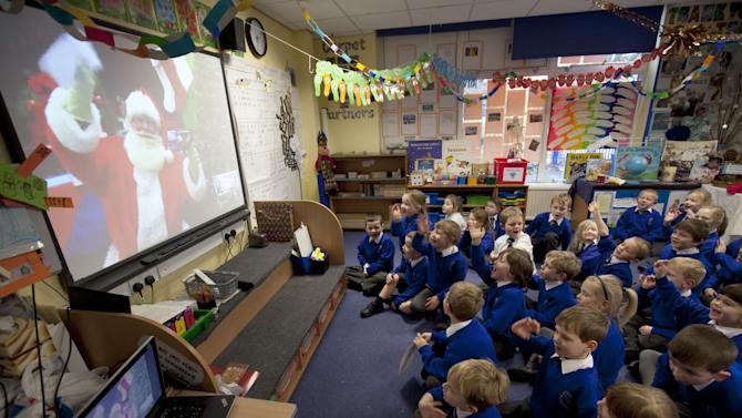 IMAGE DISTRIBUTED FOR SKYPE - Year 1 students at the Cronton Church of England Primary School, Widnes, England, wave hello to Santa via Skype.  Cronton Church of England Primary School was one of three recipients of a $10,000 technology makeover in Skype's Santa in the Classroom contest. (Jon Super/AP Images for Skype)