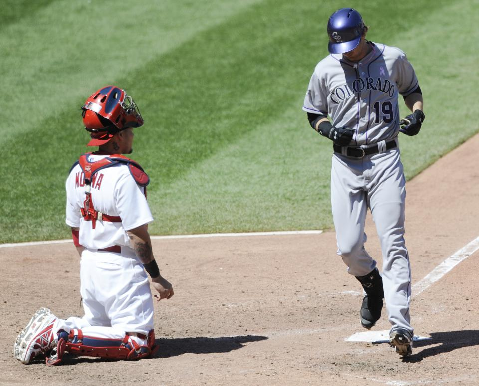 Colorado Rockies' Charlie Blackman (19) crosses the plate after his two-run home run as St. Louis Cardinals' Yadier Molina looks on in the sixth inning in a baseball game on Sunday, May 12, 2013, at Busch Stadium in St. Louis. (AP Photo/Bill Boyce)