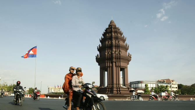 In this photo taken Feb. 25, 2013, a Cambodian motorists, transports a Buddhist monk, center, while driving past Independence Monument, in Phnom Penh, Cambodia. The Independence Monument is a striking shade of terra cotta by day and brightly illuminated by night. Glowing or not, it was constructed in 1958 to commemorate independence from the French that had been achieved five years prior. (AP Photo/Heng Sinith)