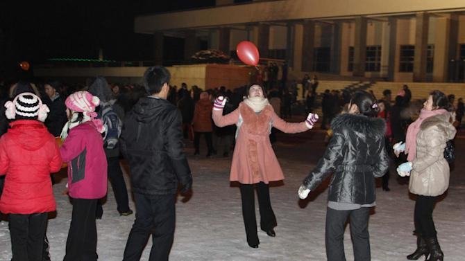 """North Koreans play with a balloon as they wait outside Pyongyang stadium for the countdown to the new year on Monday, Dec. 31, 2012 , Pyongyang, North Korea. North Koreans celebrated the arrival of the new year, marked as """"Juche 102"""" on North Korean calendars. """"Juche"""" means """"self reliance,"""" the North Korean ideology of independence promoted by North Korean founder Kim Il Sung, and modern-day North Korean calendars start with the year of his birth in 1912. (AP Photo/Kim Kwang Hyon)"""