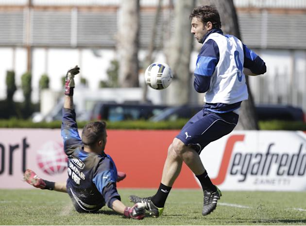 Italy's Gianmario Comi, right, tries to score past goalkeeper Francesco Bardi during a training session, in Rome, Wednesday, March 12, 2014. With three months to go before the World Cup in Brazil,