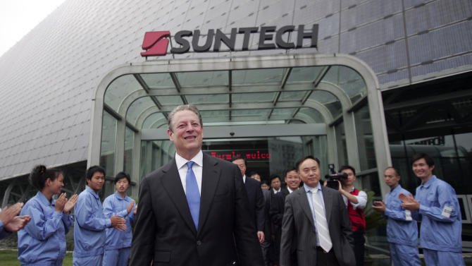 FILE - In this Friday, June 11, 2010. file photo, former U.S. Vice President Al Gore, center, visits Suntech, a solar cell factory, in Wuxi near Shanghai, China. Suntech, one of the world's biggest solar panel manufacturers, said Monday it had defaulted on a $541 million bond payment in the latest sign of the financial squeeze on the struggling global solar industry. (AP Photo)