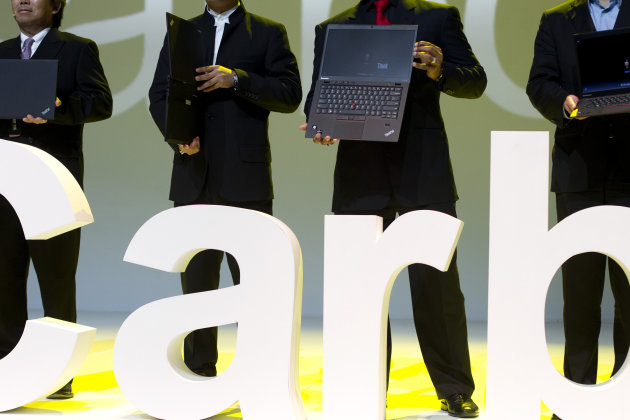 Lenovo executives hold the new ThinkPad X1 Carbon laptops in Beijing Monday, Aug. 6, 2012. The Chinese computer maker unveiled the lighter, quicker ThinkPad notebook computer inspired by the convenience of tablets and smart phones. (AP Photo/Alexander F. Yuan)