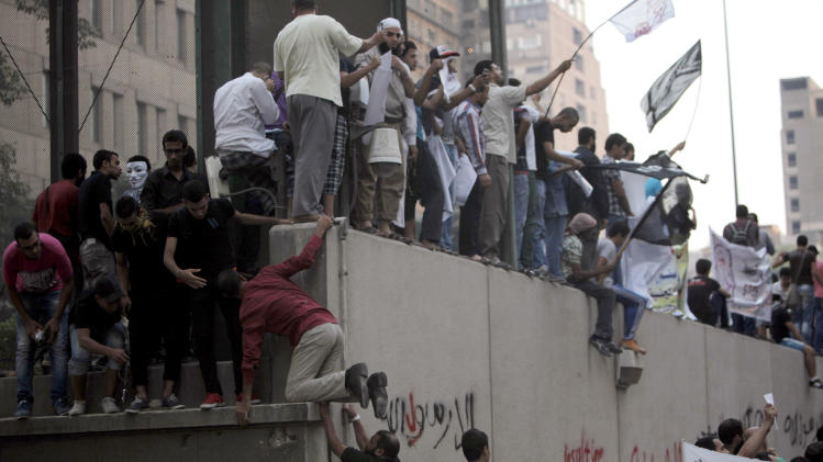 "Egyptian protesters climb the walls of the U.S. embassy with Arabic graffiti that reads ""any one but you God's prophet"" during protests in Cairo, Egypt, Tuesday, Sept. 11, 2012. Egyptian protesters, largely ultra conservative Islamists, have climbed the walls of the U.S. embassy in Cairo, went into the courtyard and brought down the flag, replacing it with a black flag with Islamic inscription, in protest of a film deemed offensive of Islam. (AP Photo/Nasser Nasser)"