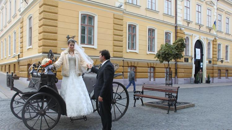 In this photo taken on Oct. 21 2012, a bride and a groom prepare for a photo session on the pedestrian-only Olha Kobylianska street in Chernivtsi, a city of 250,000  in southwestern Ukraine. Known as the Little Paris or, alternatively, the Little Vienna of Ukraine, Chernivtsi is a perfect place for a quiet romantic weekend trip and a crash course in the painful history of Europe in the 20th century. (AP Photo/Maria Danilova)