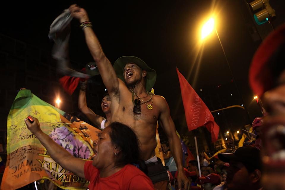 Supporters of Venezuela's President Hugo Chavez celebrate at the Miraflores presidential palace late Sunday Oct. 7, 2012. Chavez won re-election and a new endorsement of his socialist project Sunday, surviving his closest race yet after a bitter campaign against opposition candidate Henrique Capriles.(AP Photo/Rodrigo Abd)