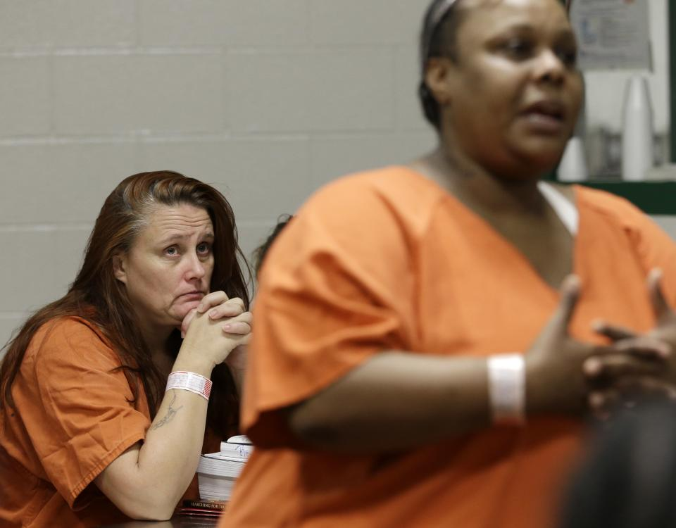 Tricia Chambers, left, watches another inmate tell her story of prostitution during a group meeting in their Harris County cell Tuesday, June 4, 2013, in Houston. Both women are part of a rehabilitation program called We've Been There Done That. (AP Photo/Pat Sullivan)