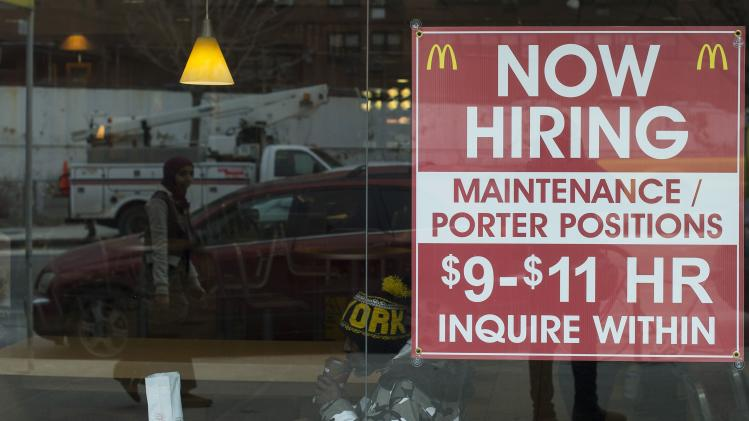 A diner sits next to a help wanted sign at a McDonalds restaurant in the Brooklyn borough of New York