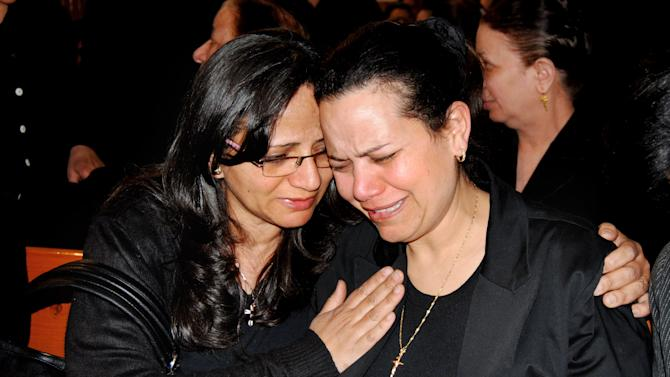 "Ragaa Abdallah, right, the wife of an Egyptian Christian who died in prison in Libya after he was detained on suspicion of having proselytized there has been buried in a subdued ceremony in his hometown, mourns during his funeral in Assuit, Egypt, Wednesday, March 13, 2012 in southern Egypt. The local church head Priest Baqi Sadaqa told the funeral congregation on Wednesday that Ezzat Atallah's death earlier this week was a ""crime against Egypt."" (AP Photo/Mamdouh Thabet)"