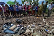 Lao villagers look at pieces of luggage from a Lao Airlines plane after it crashed into the Mekong river near Pakse town, on October 17, 2013